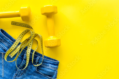 pants, bars and measuring tape for weight loss on yellow background top view moc Obraz na płótnie