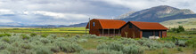 Red Farm Shed In A Big Grassland Farm Field With The Mountain On The Background.  Eastern Sierra Mountains, Mono County, California, USA