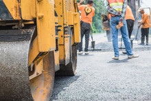 Small Asphalt Roller In On Duty Repairing Repairing Asphalt Road. Workers On A Road Construction, Industry And Teamwork.