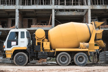 Old Yellow Cement Mixer Truck In Front Of Building Under Construction. Construction Machinery.