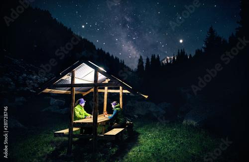 Fototapeta Tourists relaxing under starry sky in mountain landscape obraz