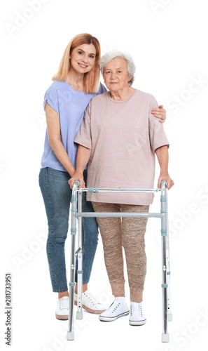Caretaker helping elderly woman with walking frame on white background Canvas Print
