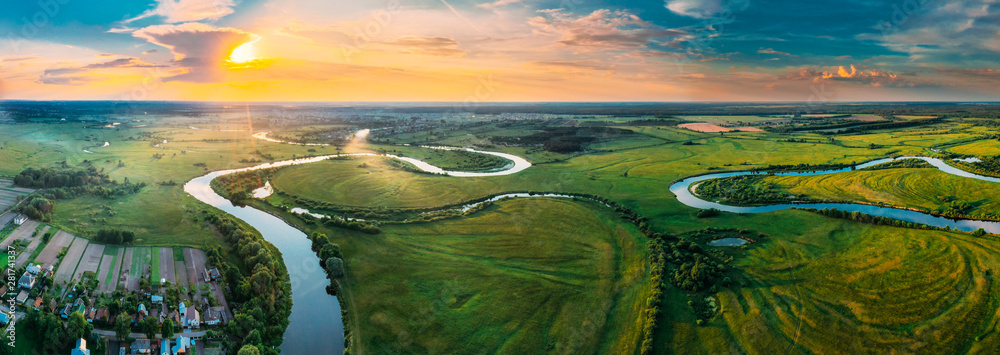 Fototapeta Aerial View Green Forest Woods Meadow And River Landscape In Sunny Spring Evening. Top View Of Beautiful European Nature From High Attitude In Summer Sunset Sunrise. Panorama, Bird's Eye View. Belarus