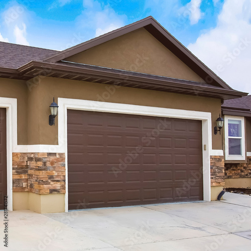 Photo Exterior of a home with two brown garage doors against cloudy blue sky