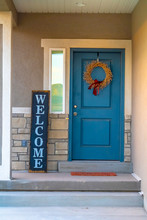 Vertical Frame Golden Wreath On The Blue Front Door Of A House With Concrete And Stone Wall