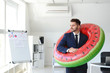 Handsome businessman with inflatable ring in office. Travel concept