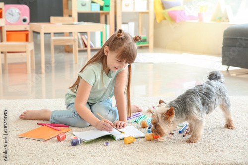 Obraz Cute little girl with dog painting while sitting on carpet - fototapety do salonu