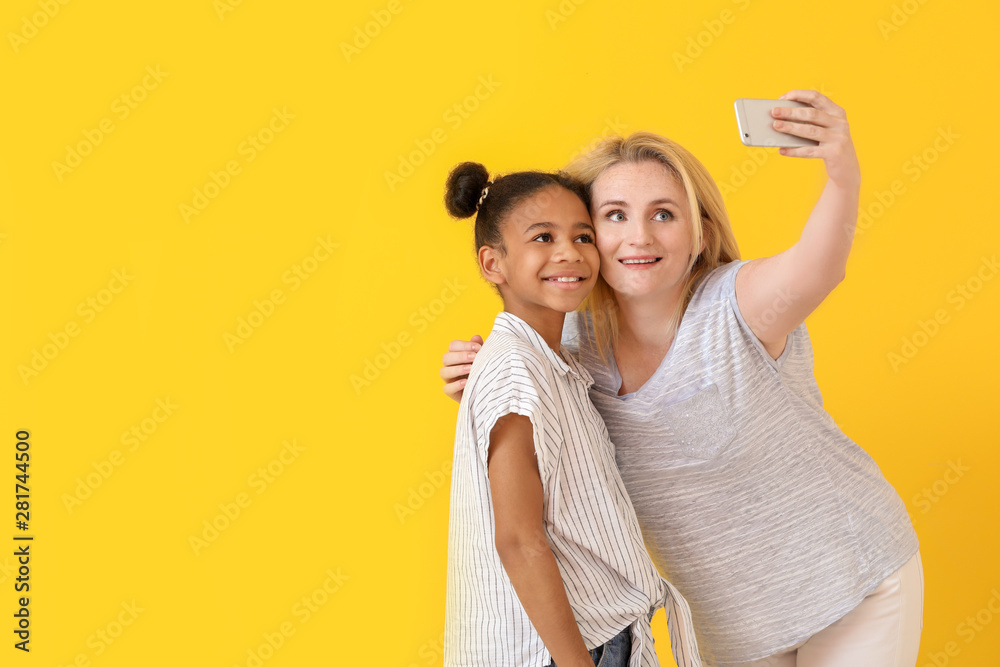 Fototapety, obrazy: Happy woman with her African-American daughter taking selfie on color background