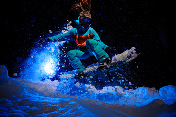 Female snowboarder dressed in a orange and blue sportswear performs tricks on the snow