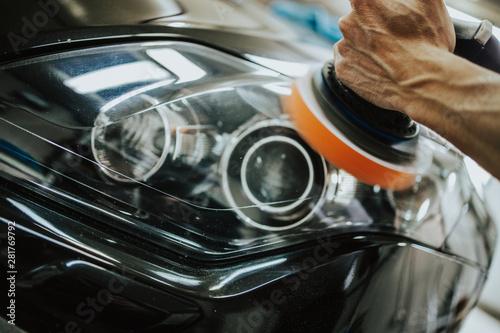 Fototapeta Car detailing - Hands with orbital polisher in auto repair shop. Selective focus. obraz