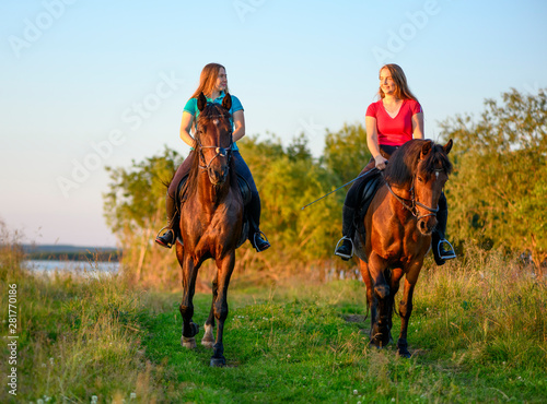 Photo Two happy teenage girls are astride their bay horses in rural in a summer evening