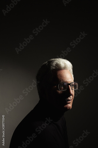 Fototapeta Fabulous at any age concept. Portrait of charismatic mature man wearing classic iconic black turtleneck and trendy eyewear over grey background with gradient. Deep shadows. Text-space. Studio shot obraz