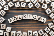 Folklore - Word From Wooden Blocks With Letters, Literary Genres Concept, Random Letters Around, Top View On Wooden Background
