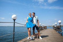 Couple, A Guy And A Girl Are Walking With A Dog On The Pier, Near The River, On A Summer Sunny Day