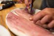 Fischgräten mit Zange aus Filet ziehen, Nahaufnahme mit zwei Gräten und Händen eines Mannes