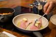 Hobbykoch legt mit Gabel Butterwürfel auf Fischfilet in Pfanne, Herd, Töpfe, Möhren, Nahaufnahme