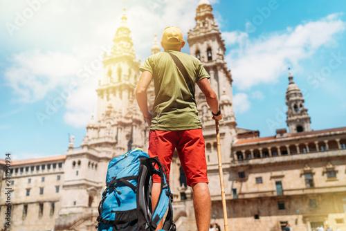 Fotografija Young pilgrim backpacker man standing on the Obradeiro square (plaza) - the main square in Santiago de Compostela as a end of his Camino de Santiago pilgrimage