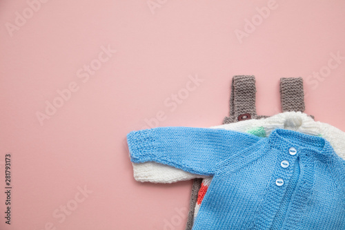 Fotografía  Cute knitted baby clothes layout on a pastel pink background