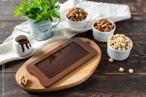 Photo Dark homemade chocolate bar in mold with different nuts on dark wooden table