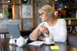 A middle-aged woman with a laptop works in a cafe in the office, she is a freelancer. A woman with glasses sits at a table with a Cup of herbal tea. She is reading.