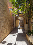 Fototapeta Na drzwi - In the summer, in the small Jerusalem courtyard there are colorful umbrellas from the bright hot sun.