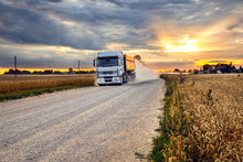Grain Truck On A Rural Road Next To A Rye Field In The Harvest Season At Sunset