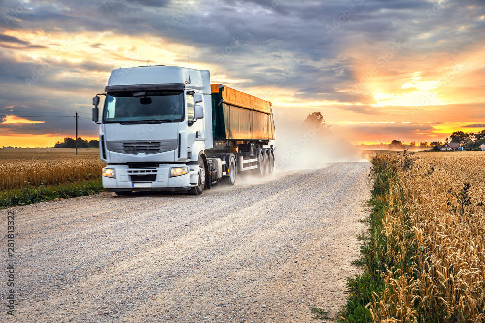 Fototapeta Grain truck on a rural road next to a rye field in the harvest season at sunset