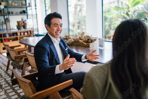A young and attractive Chinese Asian man in a well-fitted navy suit and pocket square is talking to his companion in a meeting Canvas Print