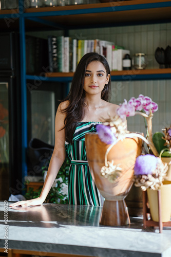 Photo A young, beautiful and elegant Indian Asian woman looks up from her floral arrangement at a counter during a morning