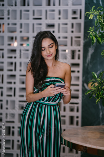 Portrait of a beautiful, young, elegant and confident Indian Asian woman smiling radiantly as she checks her smartphone Wallpaper Mural