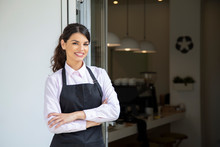 Beautiful Waitress In Apron Smiling, Showing Welcome To Coffee Shop