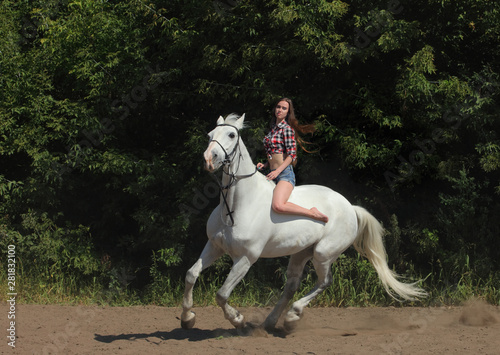 Beautiful cowgirl bareback ride her horse in woods glade at sunset Wallpaper Mural