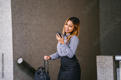 Fotografía  Portrait of a young, beautiful and tanned Malay Asian woman in a business outfit smiling radiantly as she checks her smartphone during the day