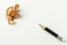 Small Used Pencil With Sharpening Shavings On White Background.