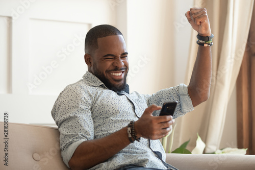 Valokuva  Overjoyed black man holding smartphone feeling euphoric with mobile win