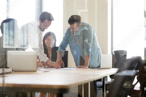 Fotografía  Happy multiethnic team working together brainstorm on paperwork in office