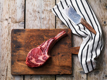 Raw Fresh Angus Meat Tomahawk On A Wooden Cutting Board With A Butcher's Knife, Top View