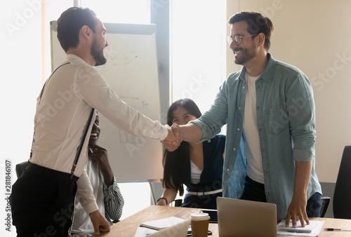 Smiling male partners greeting handshaking at diverse corporate group meeting Billede på lærred