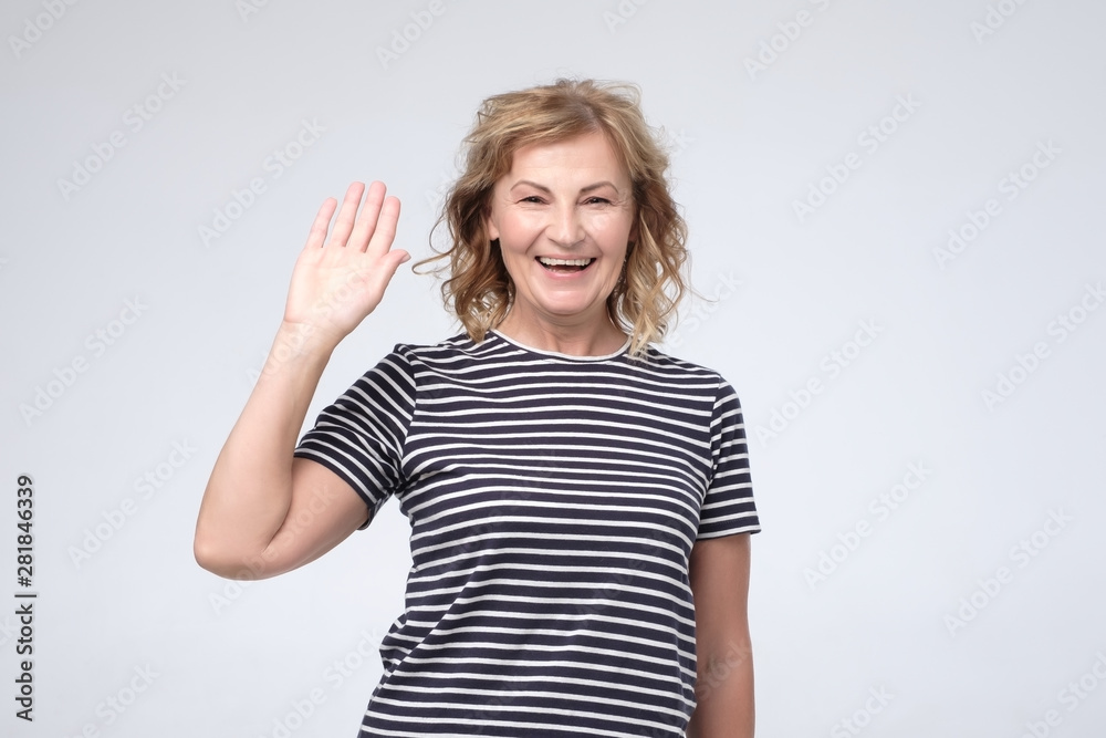 Fototapety, obrazy: Positive mature caucasian woman smiling friendly and waving hand at camera