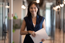 Happy Asian Businesswoman Looking At Camera Stand In Office Hallway