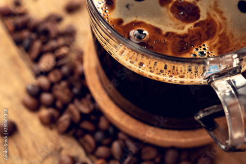 Door stickers Cafe Aromatic morning with coffee. Glass mug with coffee on an oak table. Shallow depth of field.