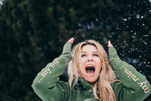 Charming Scandinavian Blonde In Green Hoodie Is Having Fun Playing With Snow In The Winter Outside