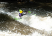 Kayaker Going Down The Rapids  Plunging Into The Waves And White Water
