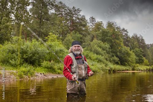 Fotobehang Vissen Mature man during fly fishing in river.