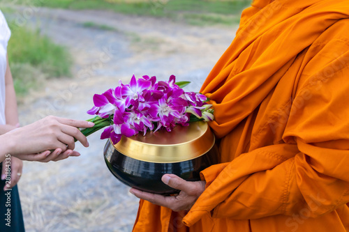 Photo Women offering orchid flowers to the monks to get alms in the morning