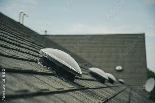 Stampa su Tela  Dome shaped solar tube skylight on asphalt shingle roof
