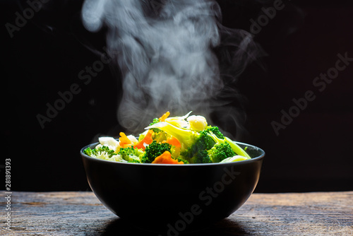 Photo The steam from the vegetables carrot broccoli Cauliflower in a black bowl, a steaming