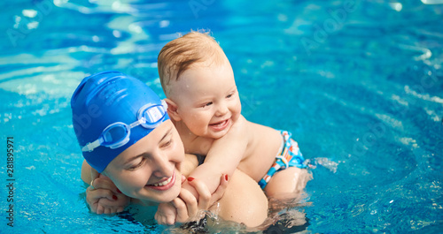 Obraz Child having fun in water with mom. Little wet boy smiling holding on his mother's back and happy woman with swimming cap and goggles. Blue turquoise water on background. Horizontal portrait view - fototapety do salonu