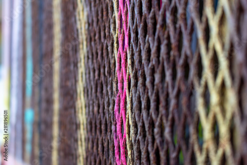 Photo  A closeup of color blend schemes on a metal grating fence
