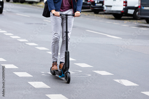 Businessman Riding An Electric Scooter On Road